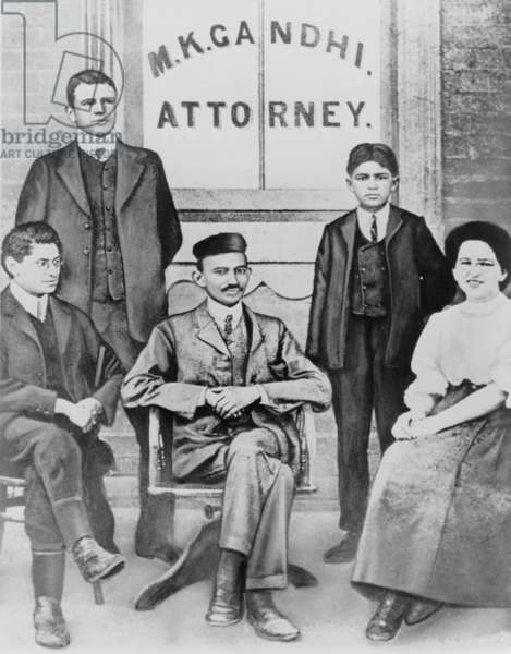 Mahatma Gandhi seated, surrounded by four associates and law clerks in South Afric. Arriving in 1893, he planned to stay only one year. After experiencing ethic discrimination, he led the Indian community's political resistance to South Africa's racism, not returning to India until 1914. c. 1900