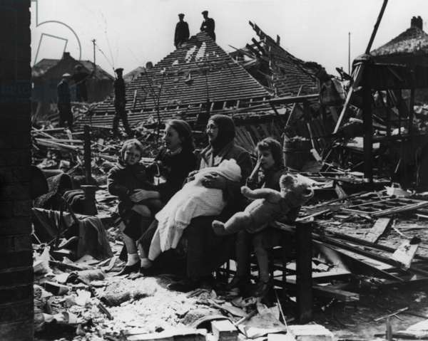 Battle of Britain, World War 2. British family seated outside their bombed home and neighborhood. c. 1940-41