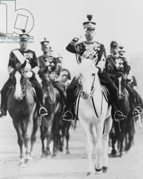 Japan's Emperor Hirohito, saluting on horseback, in military uniform, with group of Japanese officers. c. 1940