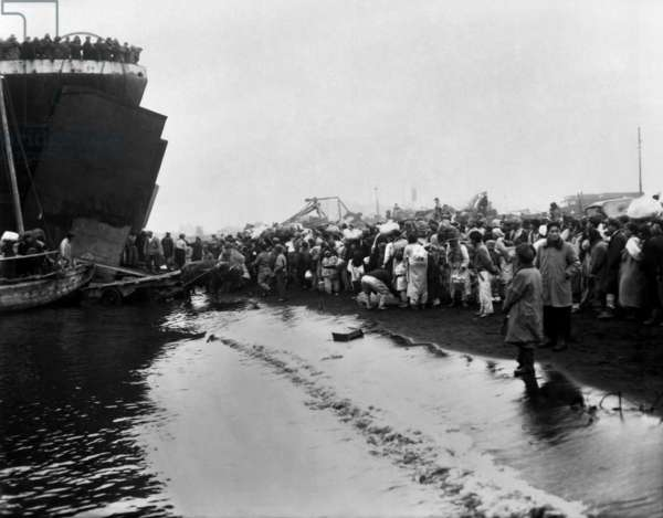 Korean refugees prepare to board an LST during the evacuation of Hungnam. They are fleeing the North Korean/Chinese troops approaching as the UN troops withdraw to South Korea. Korean War, 1950-53