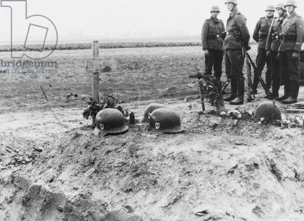 German Waffen-SS troops at the helmet topped graves of their fellows during the invasion of Poland. Sept. 1939. World War 2