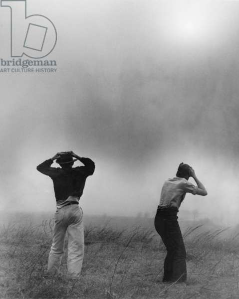 Two men hold on to their hats during dust storm, Topeka, Kansas. Ca 1950