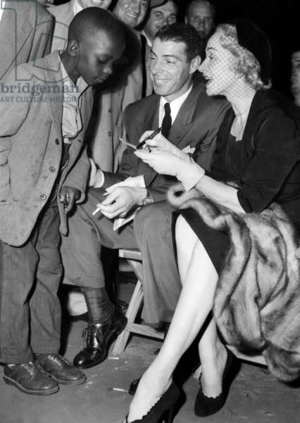 A young fan gets the autographs of Joe DiMaggio and Marlene Dietrich at a Sugar Ray Robinson fight in New York, 1951