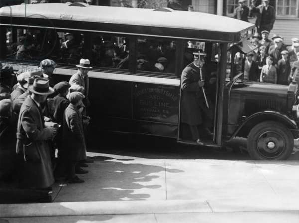 Sacco and Vanzetti taken to court on a bus of the Oakdale Community Garage and Busline. An armed officer stands in the bus door. April 9, 1927