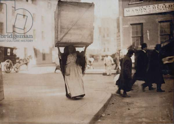 New York City, Italian woman carrying an enormous empty dry-goods box for along Bleeker Street, photograph by Lewis Wickes Hine, February, 1912