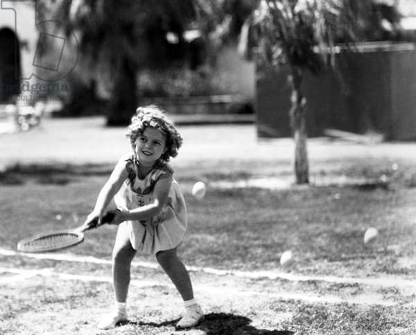 Shirley Temple, American actress, playing tennis, July 27, 1936