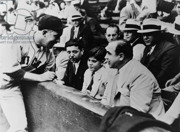 Chicago Cubs player Gabby Hartnett autographing a baseball for Sonny Capone who is sitting with his father Al Capone and other gangsters at a 1931 charity baseball game