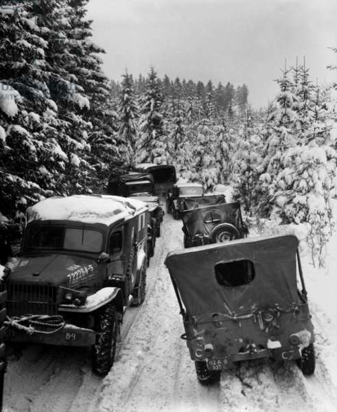 Deep snow banks on a narrow road halt military traffic in the woods of Wallerode, Belgium. After the Battle of the Bulge, Allied forces renewed their drive into Germany. January 30, 1945. World War 2