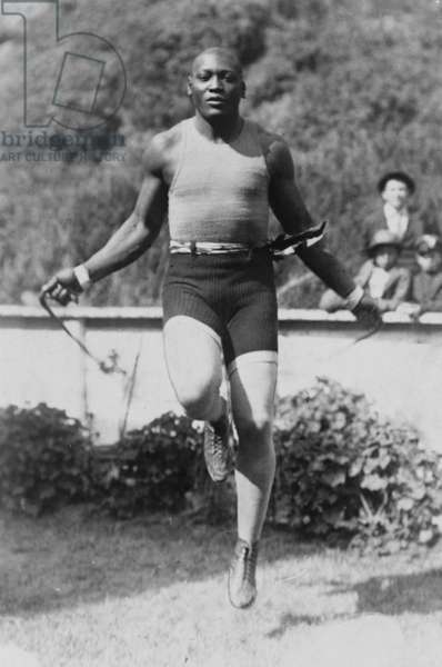 Jack Johnson (1878-1946) Heavyweight Championship of the World, with arms outstretched demonstrating his long reach. 1910. PROBLEM