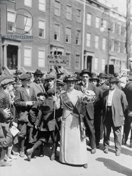 Women identified as Mrs. Suffern, is surrounded by a crowd of men and boys, while she holds a home-made banner in women suffragist parade 'Help us to win the vote.' 1914