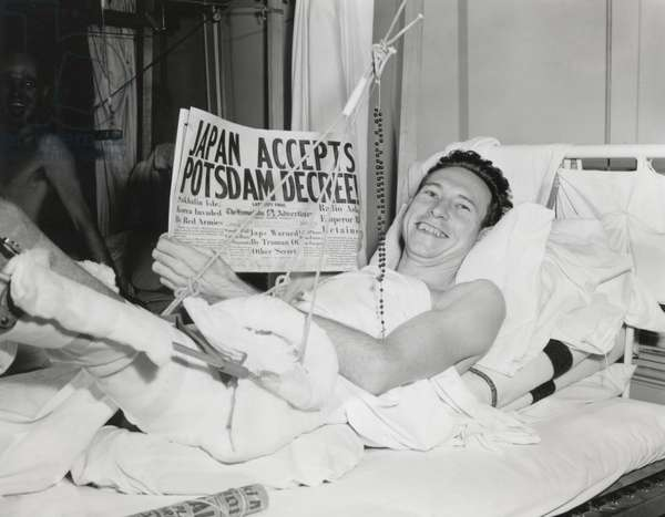 Five days before Japan's final surrender, newspaper headlines announce optimistic signs of peace. 'Japan Accepts Potsdam Decrees!' Newspaper is held by a GI recovering from wounds he received on Okinawa. August 10, 1945. World War 2