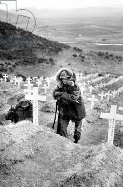Korean War: U.S. Marine visits grave of South Korean soldiers, Korea, 1951.