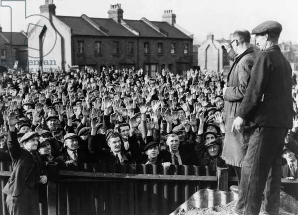 Strikers at the Royal Albert Docks, London, raising their hands in a vote of confidence for strike leader Thomas Powell, seen in right foreground, wearing glasses. 1945