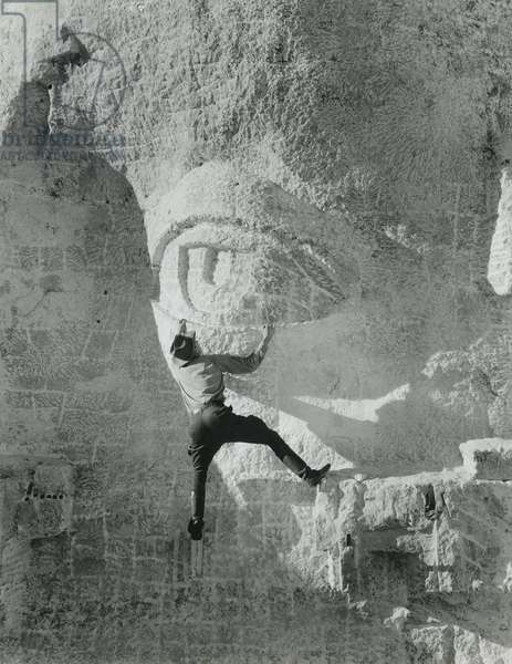 Staged photo of worker hanging from Jefferson's eye lid on Mount Rushmore. c. 1934. Photo by Charles d'Emery