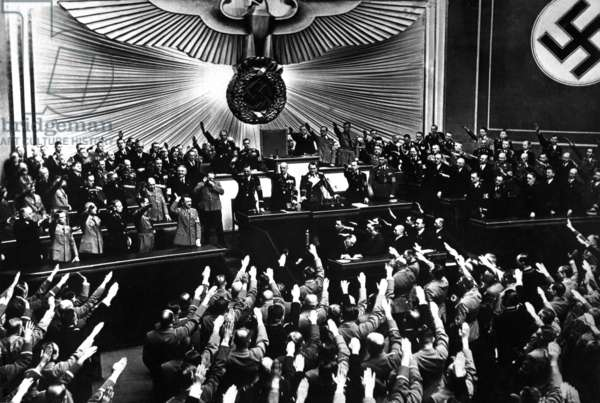 Hitler accepts the ovation of the Reichstag after the annexation of Austria. Berlin, March 1938. The Anschluss violated of the Treaty of Versailles, but remained 'peaceful' when Britain reacted only with diplomatic 'grave warnings'
