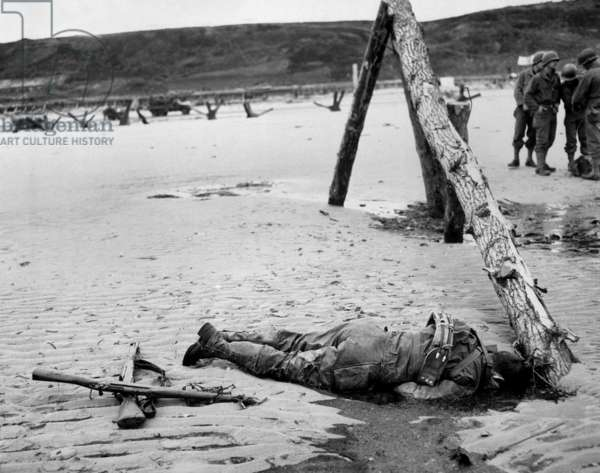 Dead U.S. soldier on Omaha beach on D-Day, June 6, 1944. Crossed rifles in the sand are a comrade's tribute. He was killed during the Normandy landings in Nazi occupied France, World War 2