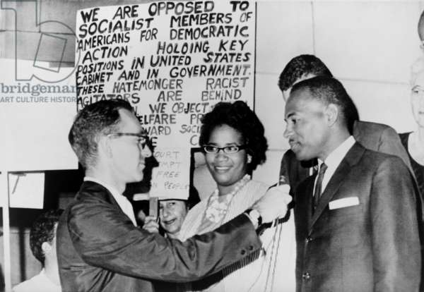 James Meredith and wife in front of segregationist poster as they talk to a reporter. The Fifth U.S. Circuit Court of Appeals ordered his admission to the University of Mississippi. Sept. 25, 1962