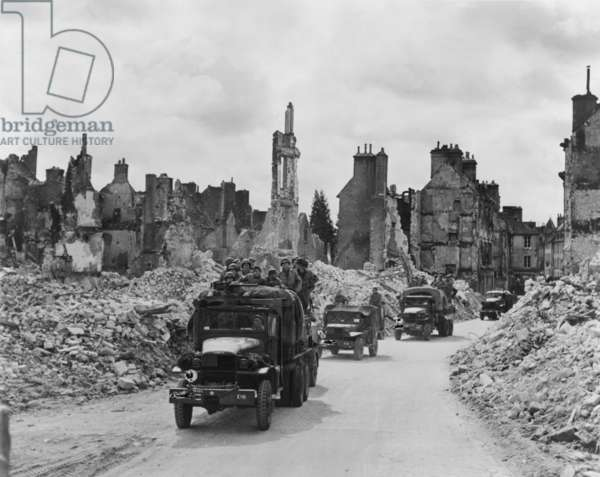 Trucks, some with U.S. soldiers standing in back, riding through the ruins Valognes, France. June-July 1944. Normandy Campaign, World War 2