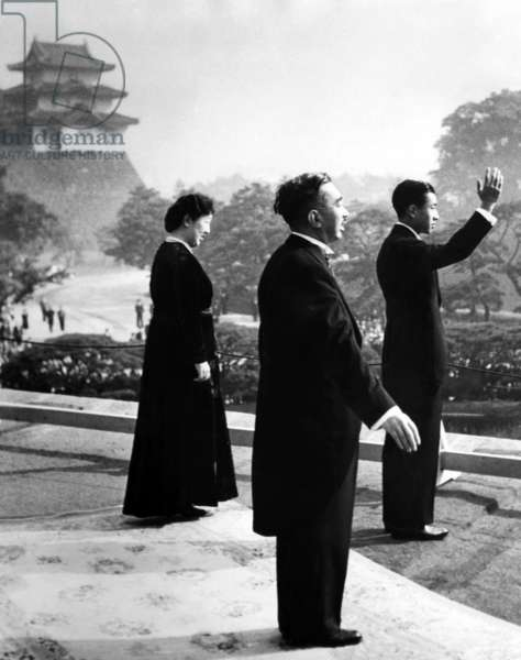 Crown Prince Akihito waves to cheering well wishers after he was proclaimed heir apparent to the throne. Behind him are his parents, Emperor Hirohito and Empress Nagako. c. 1952.