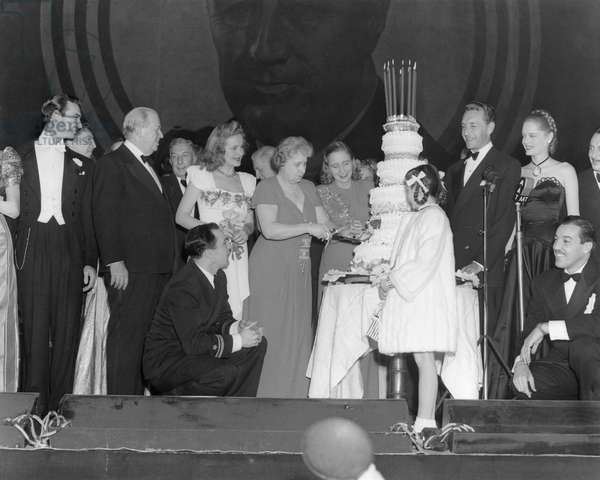 Bess and Margaret Truman at the Roosevelt Birthday Ball with Hollywood celebrities. First Lady Bess Truman and her daughter cutting the cake at the 1946 Roosevelt Birthday Ball fundraiser for the March of Dimes' fight against polio. Celebrates include: Margaret O'Brien (in front of cake); Charles Coburn (second from left); Gene Kelly (kneeling, left); Paul Henreid (third from right);, Cesar Romero (kneeling, right; Alexis Smith (second from right).