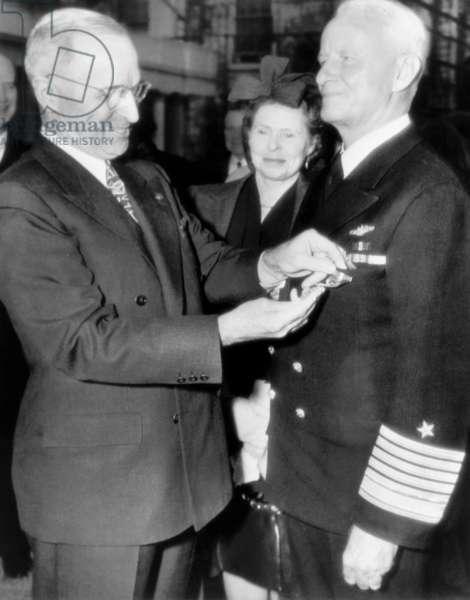 President Harry Truman, left, decorating Fleet Admiral Chester Nimitz, while Catherine Nimitz, looks on, outside the White House, October 5, 1945