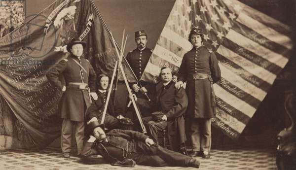 US Civil War, 1861-1865. Soldiers of the 63rd New York Infantry Regiment pose in uniform with federal and state battle flags and a rifle stack. The flags list battles the regiment fought in as part of the 'Irish Brigade'. Photo by S.J. Thompson & Co., Albany, N.Y.