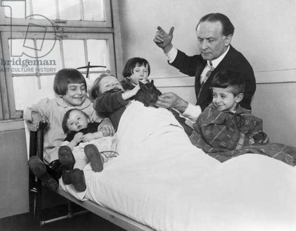 Harry Houdini and his rabbit entertain five hospitalized children. c. 1925