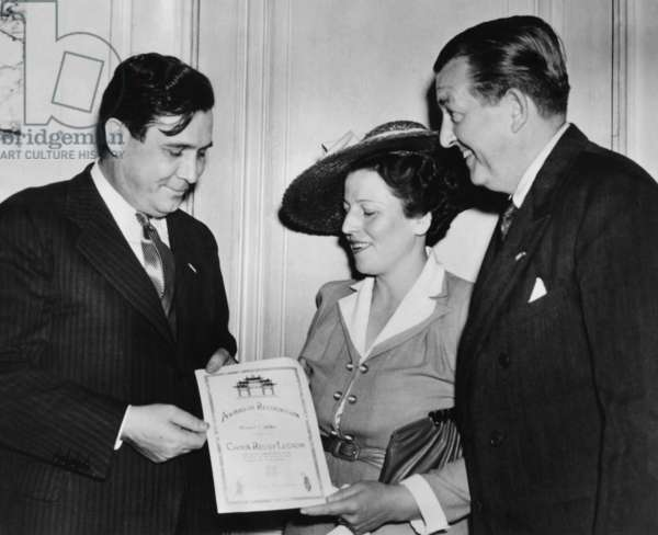 Author Pearl Buck presents Wendell Willkie with a United China Relief Fellowship Certificate. United China Relief was founded in 1941 in NYC to raise funds to aid the Chinese people during World War II. At right is James G. Blaine