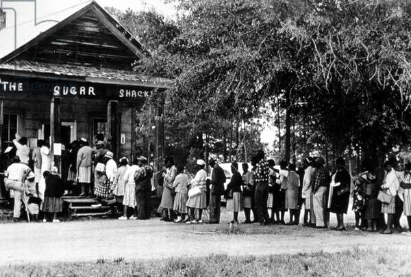 African Americans line up to vote at store in Alabama election, 1966.