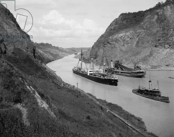 Boats move through Panama Canal at the Culebra Cut (Gaillard Cut), which crosses the continental divide. At center right is a suction dredge to maintain canal depth. c. 1910-14