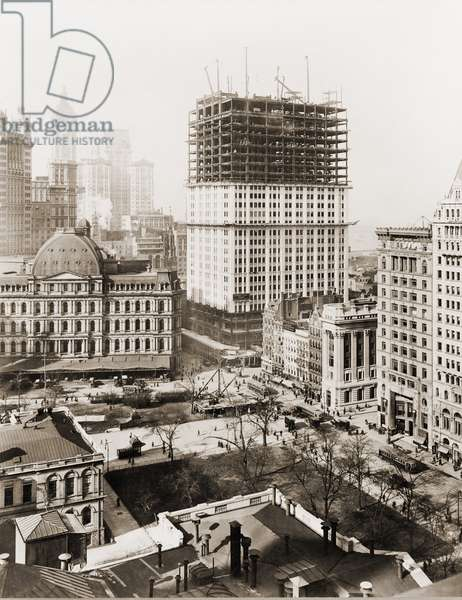 Woolworth Building, partially-constructed building amidst smaller buildings. The lower floors have received a white terra-cotta facing worked in lacy Gothic style. Photo made April 4th, 1912