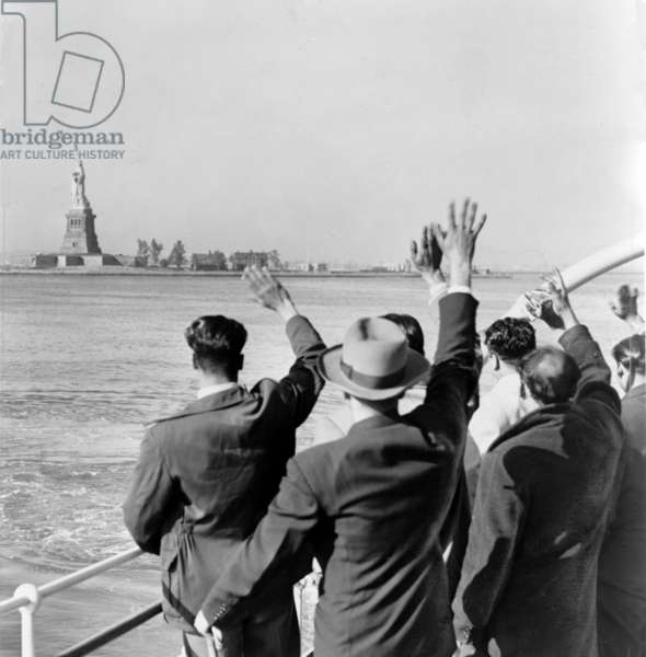 Statue of Liberty. Part of a group of 171 illegal immigrants wave goodbye to the Statue of Liberty from the Coast Guard cutter that took them from Ellis Island to the Home Lines ship Argentina in Hoboken for deportation. 1952