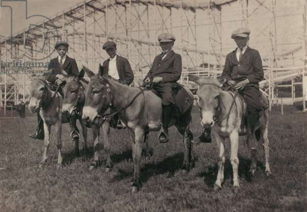 Young men on donkeys, original caption: 'Sandy Beach, Sunday recreation - mill boys 14-16', Fall River, Massachusetts, photograph by Lewis Wickes Hine, June, 1916