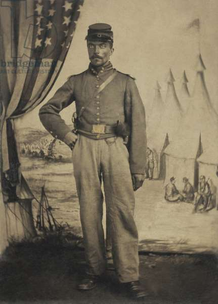 African American Civil War soldier in Union artillery jacket with shoulder scales, 1863-65. Shoulder scales were jointed brass epaulets worn more commonly in the western theaters of the US Civil War. He stands in front of a painted backdrop showing military camp