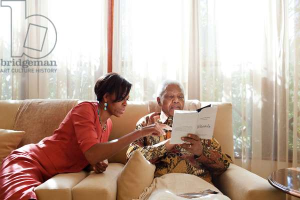 First Lady Michelle Obama meets with former President Nelson Mandela of South Afric. At Mandela's home in Houghton, South Africa, June 21, 2011. Mandela holds a book, 'Mandela by Himself, The Authorized Book of Quotations'