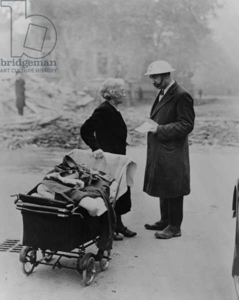 A bombed out London women carrying a few belongings talks with an Air Raids Precautions worker. 1940 during the Battle of Britain in World War 2