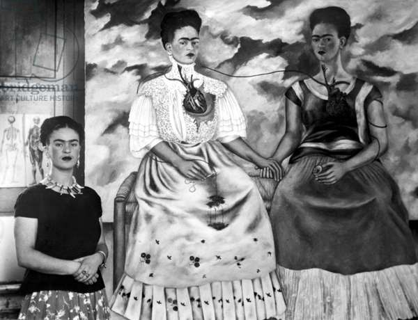 Frida Kahlo shown with her painting Me Twice. The painting shows Kahlo as a 19th century lady linked by an artery to herself dressed as an Indian. Surgeon's clip stops bleeding near her right hand to indicate she is childless. 10-23-39