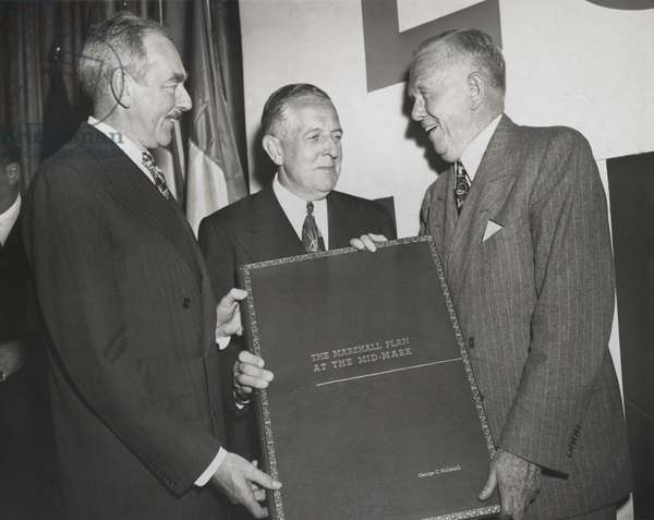 Celebration of the 2nd Anniversary of the Marshall Plan. Secretary of State Dean Acheson (left) and Economic Cooperation Administrator Paul Hoffman (center) present George Marshall a large bound report on operation of the Marshall Plan. April 3, 1950.