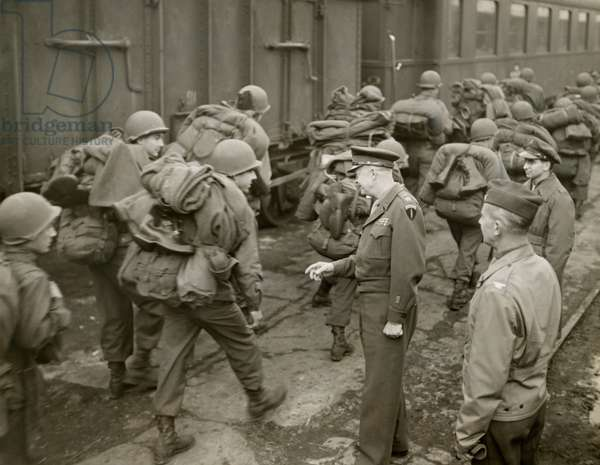 General Dwight Eisenhower greets GI's loaded down with full packs as they arrive at a French port. Feb. 25, 1945