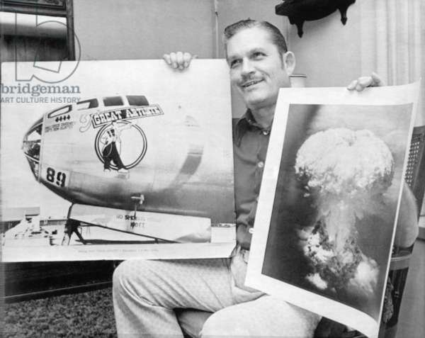 Atomic Bomb. Kermit Beahan, bombardier on the plane that dropped the atomic bomb on Nagasaki, August 9, 1945. He holds a picture of the plane that flew instruments on that flight and a photo he took of the blast at Nagasaki. Houston, Texas, 1973