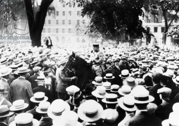 Policeman drives his horse through the crowds on Boston Common during a Sacco-Vanzetti protest. Speakers and Spectators were arrested. 1927.