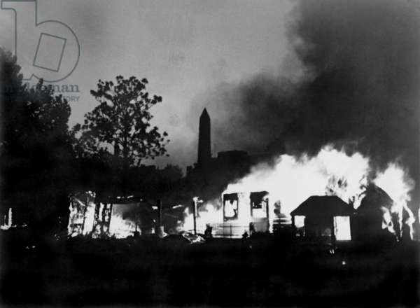 The Bonus Marcher's protest ended with a fire, set by U.S. Army, consuming the camp of Bonus Expeditionary Forces. The Washington Monument is in the background. July 29, 1932