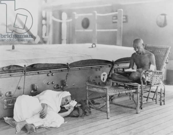 Mahatma Gandhi (1869-1948), leader of the Indian independence movement, on the S.S. Rajputna, enroute to the Round Table Conference in London. His disciple, Madeline Slade, renamed Mirabehn by Gandhi, lies on the nearby deck. 1931