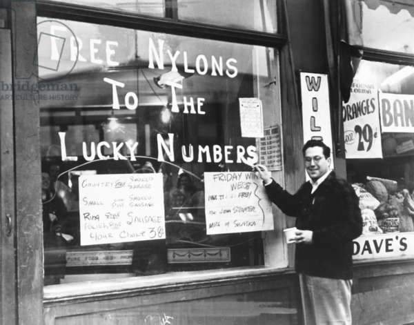 Cleveland grocer Max Astor promoting his grocery store with 'Free Nylons to the Lucky Numbers'. Nov. 5, 1946. He posts his meat specials, all of which are sausage. Shortages of foods and consumer goods continued after the end of World War II