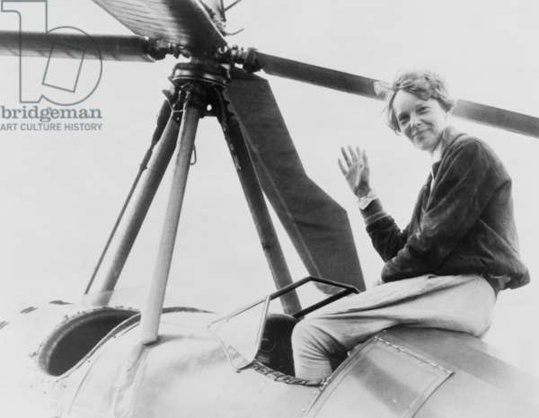 Amelia Earhart (1897-1937), waving, seated outside cockpit on top of an Autogiro, in Los Angeles, shortly after she became the first woman to complete a solo coast-to-coast flight. August 1932
