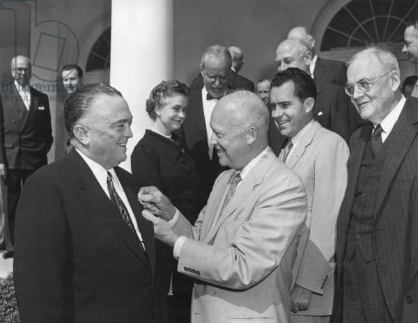 President Eisenhower presents the National Security Medal to FBI Director J. Edgar Hoover. Ceremony attended by a Cabinet group which included: Oveta Culp Hobby, Allen Dulles, Richard Nixon, and John Foster Dulles. May 27, 1955. In far left background is Nelson Rockefeller.