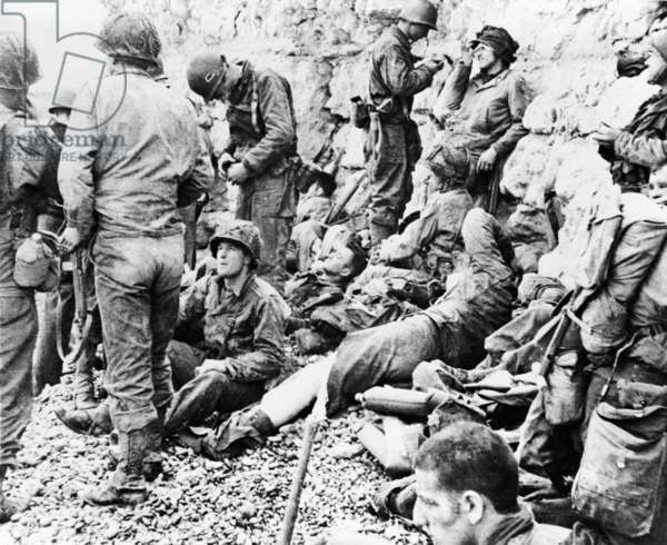 D-Day in Normandy, France. Allied assault troops relaxing before a protective chalk cliff overlooking the invasion shore, Normandy, France. June 6-7, 1944