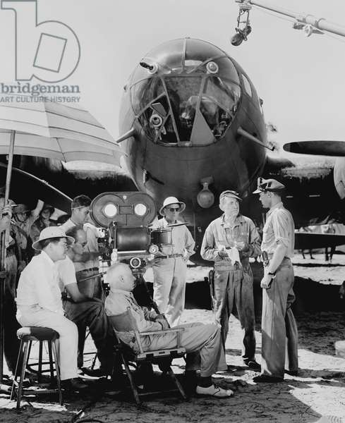 AIR FORCE, from left: cinematographer James Wong Howe (pith helmet), director Howard Hawks (in chair) filming Harry Carey, John Ridgely on set, 1943