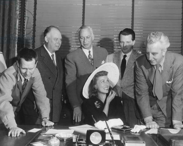 THE DIARY OF A CHAMBERMAID, Paulette Goddard (seated) signs her contract to appear in the film as from left: Burgess Meredith, director Jean Renior, Charles W. Koerner, William Dozier, screenwriter Dudley Nichols look on, 1946