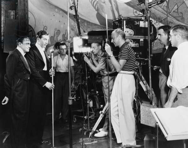 THE BIG BROADCAST OF 1937, from left: Jack Benny, Ray Milland, director Mitchell Leisen (striped shirt), cinematographer Theodor Sparkuhl (behind camera) filming on set, 1936